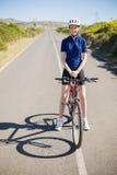 Donna sorridente con la bici sulla strada principale Fotografie Stock Libere da Diritti