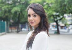 Donna sorridente con la blusa bianca in un parco Immagini Stock
