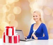 Donna sorridente con la carta di credito ed il computer portatile Fotografia Stock Libera da Diritti