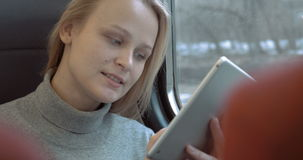 Donna sorridente con la compressa in treno video d archivio