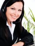 Donna sorridente con la cuffia in ufficio fotografia stock libera da diritti
