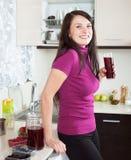 Donna sorridente con la frutta-bevanda rossa Immagini Stock