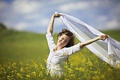Donna sorridente con la parte del panno bianca in vento Immagini Stock
