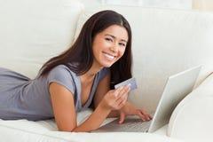 Donna sorridente con la scheda a disposizione che si trova sul sofà Immagini Stock Libere da Diritti
