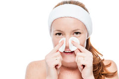 Donna sorridente con le lentiggini che puliscono il suo fronte con i cuscinetti di cotone Fotografie Stock Libere da Diritti