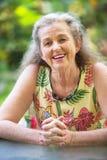 Donna sorridente con le mani piegate fotografie stock