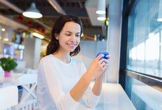 Donna sorridente con lo smartphone al caffè Immagini Stock