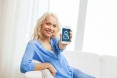Donna sorridente con lo smartphone a casa Fotografia Stock Libera da Diritti