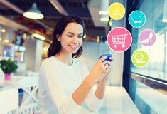 Donna sorridente con lo smartphone che compera online Immagine Stock