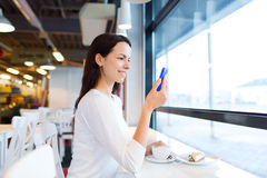 Donna sorridente con lo smartphone ed il caffè al caffè Immagine Stock Libera da Diritti