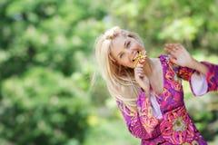 Donna sorridente con lolipop luminoso sulla natura Fotografie Stock Libere da Diritti