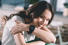 Donna sorridente con smartwatch sul polso fotografia stock libera da diritti