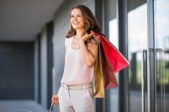 Donna sorridente con tre sacchetti della spesa che esamina distanza Immagine Stock Libera da Diritti