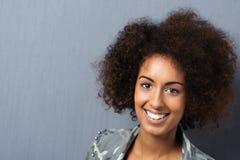Donna sorridente con un'acconciatura riccia di afro Fotografia Stock Libera da Diritti