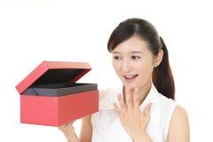 Donna sorridente con un regalo Fotografia Stock