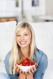 Donna sorridente con una ciotola di fragole Fotografia Stock