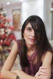 Donna sorridente con una priorità bassa dell'albero di Natale Immagine Stock