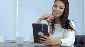 Donna sorridente in cuffie che hanno video chiamata tramite compressa digitale in un caffè archivi video