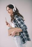 Donna sorridente in cuffie con i taccuini in mani Fotografia Stock