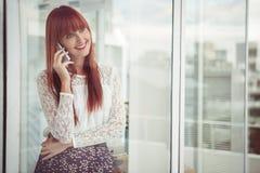 Donna sorridente dei pantaloni a vita bassa che ha una telefonata Fotografia Stock Libera da Diritti