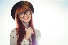Donna sorridente dei pantaloni a vita bassa che posa con una matita Immagini Stock