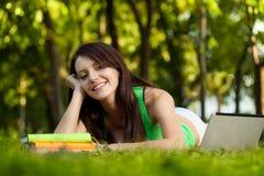 Donna sorridente del brunette che pone sull'erba Fotografie Stock