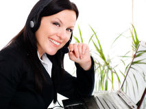 Donna sorridente del brunette con la cuffia in ufficio immagine stock libera da diritti