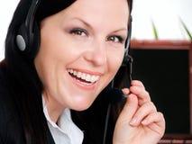 Donna sorridente del brunette con la cuffia in ufficio Fotografia Stock Libera da Diritti