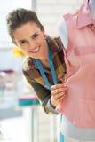 Donna sorridente del sarto che guarda fuori dal manichino Fotografie Stock Libere da Diritti