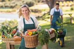 Donna sorridente dell'agricoltore che tiene un canestro di verdure Immagini Stock