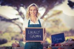 Donna sorridente dell'agricoltore che tiene un segno coltivato sul posto Fotografia Stock