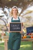 Donna sorridente dell'agricoltore che tiene un segno coltivato sul posto Fotografie Stock
