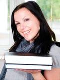 Donna sorridente dell'allievo con i libri della holding dello zaino Fotografia Stock
