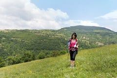 Donna sorridente dell'alpinista con lo zaino nella montagna Fotografia Stock