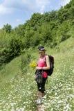Donna sorridente dell'alpinista con lo zaino su un prato con i fiori Fotografie Stock