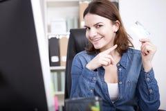 Donna sorridente dell'ufficio alla sua Tabella che mostra una carta Immagine Stock Libera da Diritti