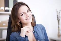Donna sorridente dell'ufficio che esamina la macchina fotografica Fotografia Stock
