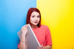 Donna sorridente della testarossa con un computer portatile premio grigio in sue mani Fotografia Stock Libera da Diritti