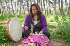 Donna sorridente dello sciamano con il tamburo messo all'altare fotografia stock libera da diritti