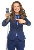 Donna sorridente di affari che indica sul microtelefono del telefono immagini stock