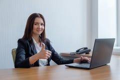Donna sorridente di affari che lavora al computer portatile e che spinge i pollici su immagini stock libere da diritti