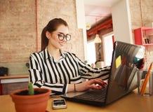 Donna sorridente di affari che lavora allo scrittorio con il computer portatile nell'ufficio Immagine Stock
