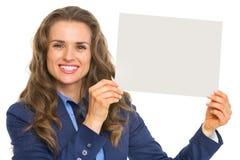 Donna sorridente di affari che mostra lo strato della carta in bianco Fotografie Stock
