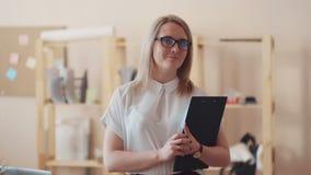 Donna sorridente di affari che scrive le note alla lavagna per appunti all'ufficio video d archivio