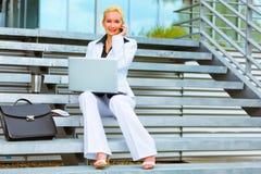 Donna sorridente di affari con il computer portatile che comunica sul fon Fotografia Stock Libera da Diritti