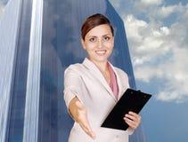 Donna sorridente di affari con la scheda di clip a disposizione Immagine Stock
