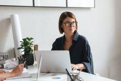 Donna sorridente di bellezza in occhiali che si siedono dalla tavola Immagine Stock Libera da Diritti