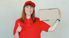 Donna sorridente di consegna in uniforme rossa Femmina in cappuccio, in maglietta, in jeans che funzionano come corriere o in com video d archivio