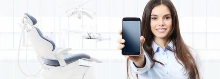 Donna sorridente di cure odontoiatriche che mostra Smart Phone sulla clinica del dentista immagini stock libere da diritti