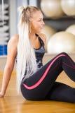 Donna sorridente di forma fisica che si siede in attrezzatura di allenamento alla palestra Fotografie Stock Libere da Diritti